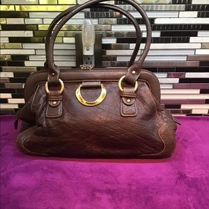 A brown vinyl satchel medium sized handbag.